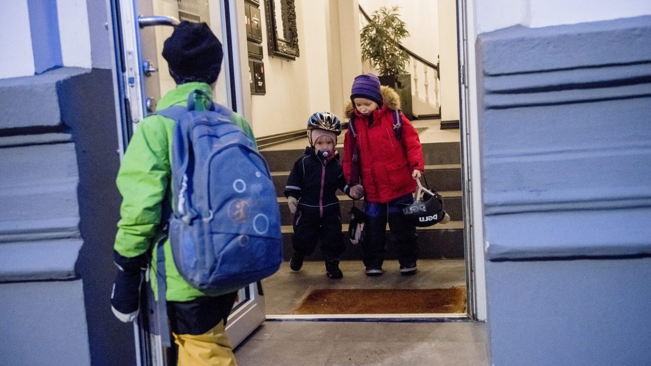 Three children on their way out of the front door of an apartment in Vika.