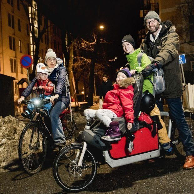 A family of two bikes. An electric bicycle loaded with both children and backpacks.